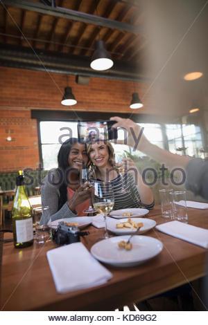 Femme avec téléphone appareil photo photographier les amis manger, boire le vin blanc au restaurant table Banque D'Images