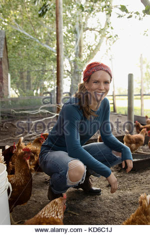 Portrait smiling female farmer avec les poulets dans poulailler Banque D'Images