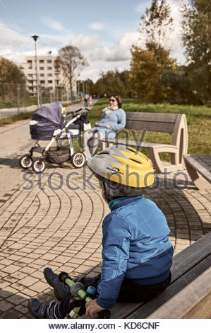Casque avec garçon assis sur un banc en bois, près d'une femme avec bébé buggy sur octobre 2017 à Poznan, Pologne Banque D'Images
