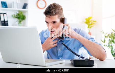 Beau jeune homme pensif avec phone and looking at laptop dans le bureau. Banque D'Images