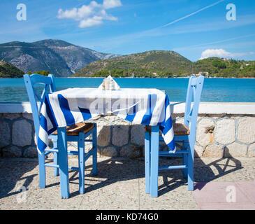Tableau bleu avec deux chaises plus drapeau grec cirée dans un restaurant en bord de mer, dans la capitale de Vathy Banque D'Images