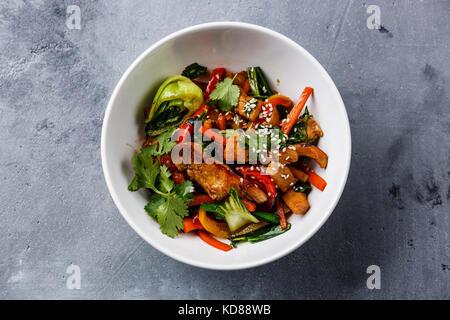 La viande de poulet avec légumes sautés dans un bol sur wok sur fond de béton Banque D'Images