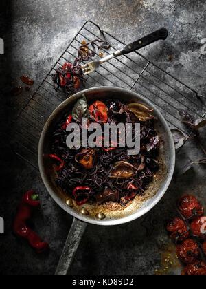 Pan rustique rempli de noir, l'encre de seiche les pâtes et tomates rôties sur une surface rustique foncé. Banque D'Images