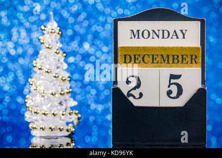 Calendrier en bois et l'arbre de Noël la réflexion sur une table en verre sur fond bleu Banque D'Images
