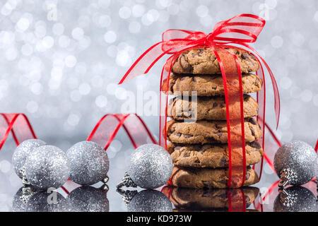 Pile de cookies aux pépites de chocolat avec des ornements de Noël réflexion sur la table en verre sur fond argenté Banque D'Images