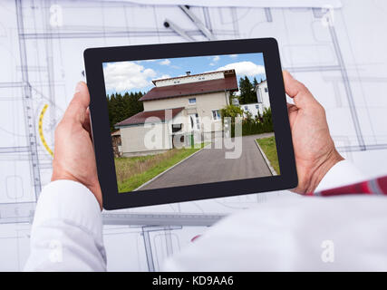 Close-up of male architect holding digital tablet over blueprint Banque D'Images