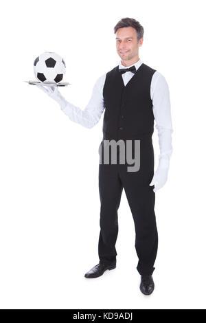 Portrait of happy waiter holding football dans le bac