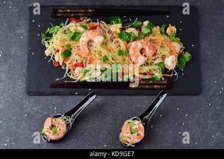 Nouilles aux crevettes et légumes sur une plaque de pierre noire et de cuillères à soupe traditionnelle sur un fond Banque D'Images