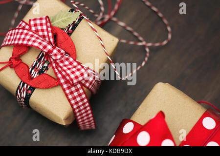 Cadeaux de Noël, décoration rétro, étoiles et ruban rouge à carreaux, enveloppé dans du papier craft Banque D'Images