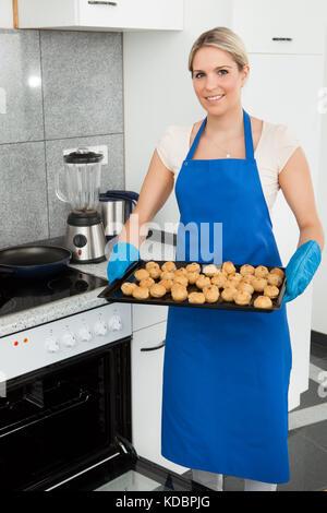 Jeune femme avec le bac plein de cookies du four Banque D'Images