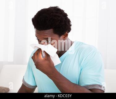 Jeune homme africain ayant un tissu froid holding et en soufflant son nez Banque D'Images