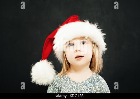 Noël des enfants girl in santa hat rêver sur fond noir