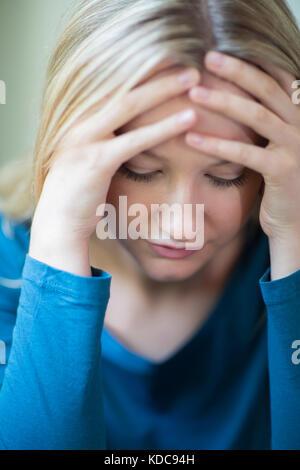 Jeune femme souffrant de dépression with head in hands Banque D'Images