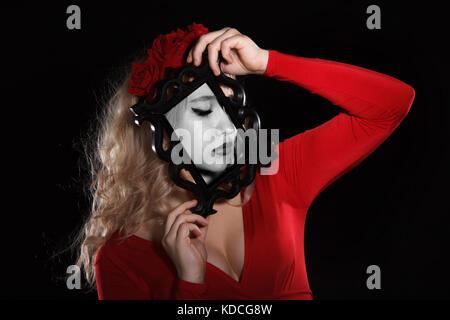 Jolie Jeune femme tenant un cadre devant son visage sur fond noir Banque D'Images