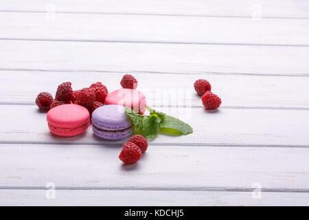 Macarons rose avec des framboises et de la menthe sur fond de bois blanc Banque D'Images