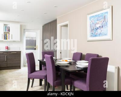 Une table à manger en bois foncé avec des chaises violettes, défini pour un repas dans la cuisine contemporaine Banque D'Images