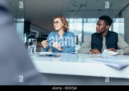 L'écoute de la femme, son collègue au cours de réunion. Les créatifs de discuter affaires en salle du conseil. Banque D'Images