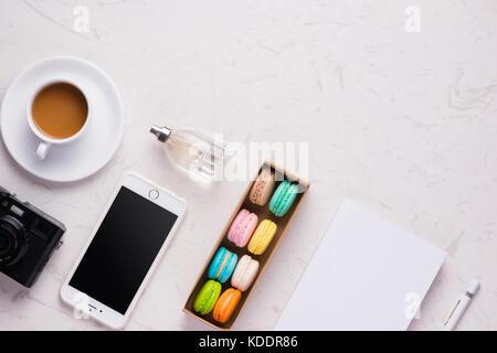 Bureau Bureau femme avec les cosmétiques, tablette numérique, tasse de café et macarons colorés, vue du dessus Banque D'Images