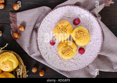 Délicieux caramel profiteroles crème de noix sur une plaque de céramique sur un fond de bois foncé. vue d'en haut. Banque D'Images