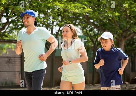 Une famille heureuse de trois cours d'exécution sur route en matin d'été Banque D'Images