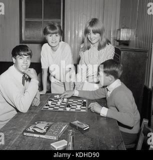 Années 1960, historique, quatre jeunes gens dans un village hall, avec les deux garçons assis à une table jouant un jeu de dames, avec les deux filles à côté d'eux, England, UK.