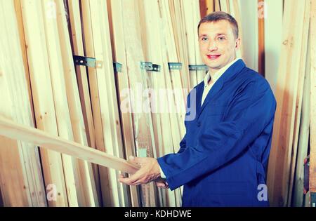 Ouvrier américain long debout avec planche en bois dans l'atelier Banque D'Images