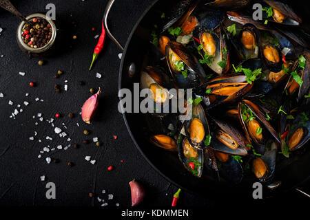 Les moules dans une sauce au vin avec des herbes dans une poêle sur un fond noir. Télévision. vue d'en haut. Banque D'Images