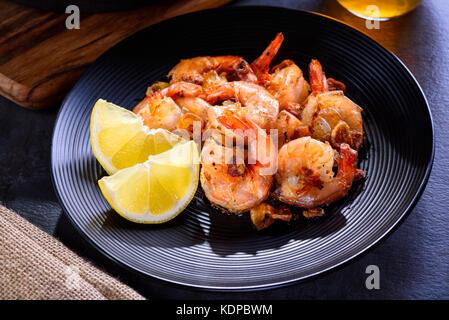 Crevettes géantes grillées poêle sur une plaque noire.. Gros plan de tranches de rôti crevettes ail et d'épices. Banque D'Images