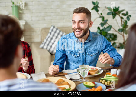 Jeune homme de dîner avec des amis Banque D'Images