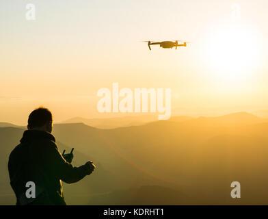 Silhouette de jeune homme à l'aide de drone au coucher du soleil pour les photos et video making - homme heureux Banque D'Images
