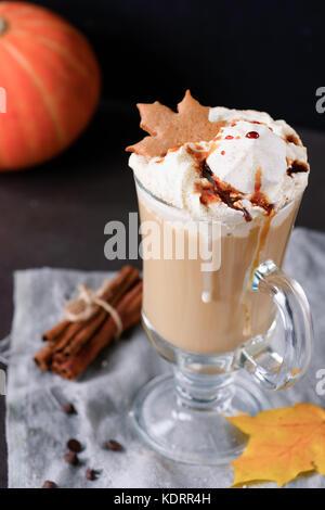 Pumpkin spice latte avec crème fouettée, sirop de caramel et les guimauves dans un mug décoré avec gingerbread cookie. Banque D'Images
