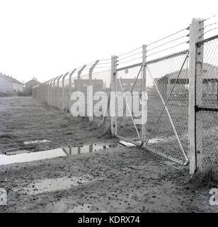 Années 1960, historique, Angleterre, Royaume-Uni, clôtures métalliques avec des barbelés sur le dessus et des grilles verrouillées protéger et bloquer toute entrée illégale dans une vieille cour d'entreposage industriel sur le bord d'une grande cité.