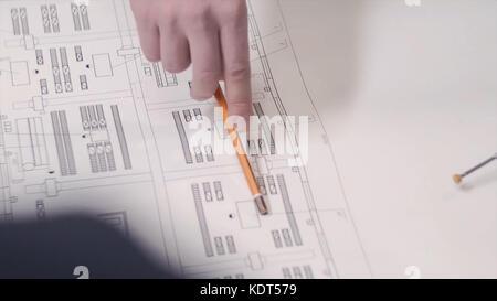Un homme montre à l'aide d'un crayon sur un dessin ou modèle sur la table. homme montrent les plans de construction Banque D'Images