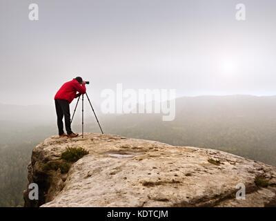 Photographr à viseur dans Appareil photo numérique reflex numérique de position sur trépied. photographie de l'artiste Banque D'Images