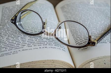 Paire de lunettes à l'envers posé sur un livre religieux Banque D'Images