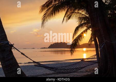 Magnifique lever de soleil sur plage de sable sur l'île de Bintan en Indonésie avec silhouette de hamac et cocotiers Banque D'Images
