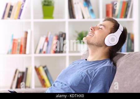 Vue côté détente portrait d'un homme assis sur un canapé à l'écoute de musique portant des écouteurs Banque D'Images