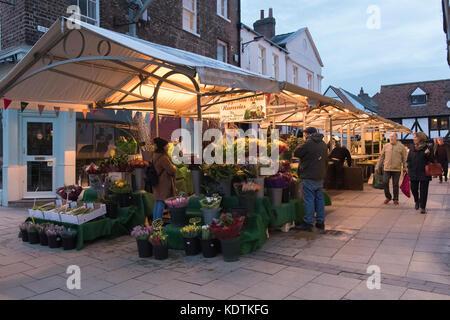 Soir dans le centre de York avec des gens qui marchent par allumé en pagaille les étals de marché commerçant et Banque D'Images