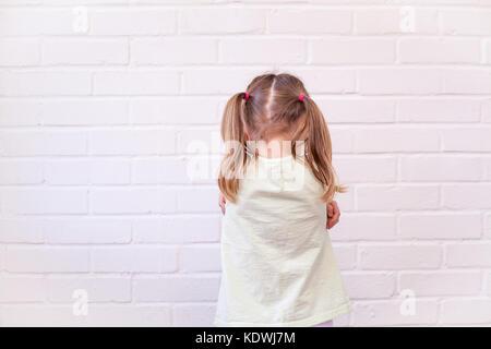 Enfant de sexe féminin avec retour au spectateur et bras croisés en triste ou grincheux posent contre un mur de Banque D'Images