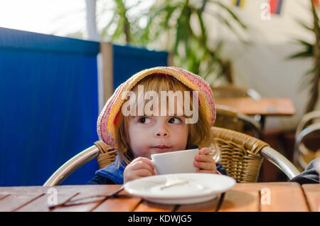 Little White Caucasian Blonde Girl Wearing Pink Hat été assis à la table de boire du lait chaud à partir de la Tasse Banque D'Images