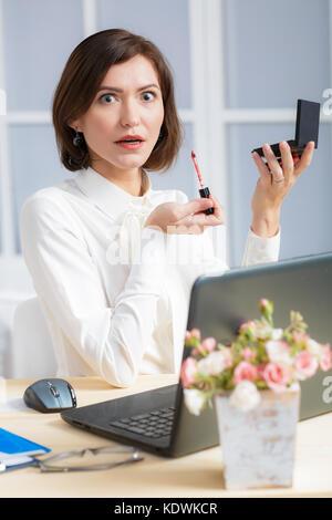Femme d'affaires au bureau de maquillage Banque D'Images