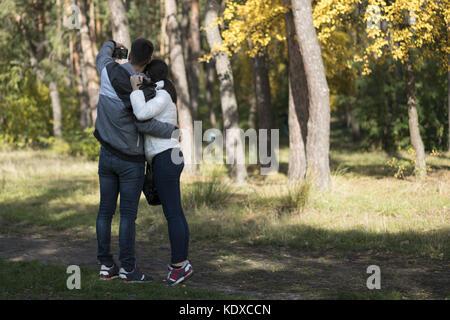 Un jeune couple faisant l'amour dans le parc selfies. Vue de dos. Banque D'Images