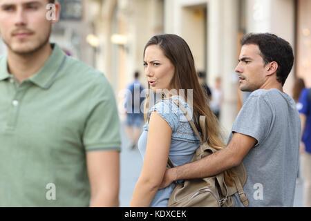 Femme infidèle à un autre homme et son petit ami en colère la regardant dans la rue Banque D'Images
