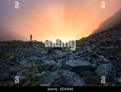 Homme debout devant de la lumière solaire à soirée d'été dans l'île de Lofoten montagne Banque D'Images