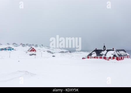 Vieux bâtiment rouge et des Inuits maisons en arrière-plan parmi la neige au fjord, Nuuk Groenland Banque D'Images