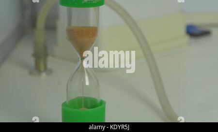 Le sable dans les vases du sablier mesurant le temps qui passe dans un compte à rebours pour un sablier. Banque D'Images