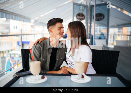 Jeune romantique Valentine couple in love kissing in cafe. franc vue à travers la fenêtre en verre. Banque D'Images