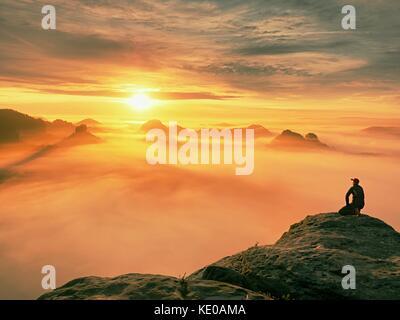 Moment de solitude sur le sommet rocheux exposés. man in black profitez d'une vue merveilleuse. s'asseoir sur le Banque D'Images
