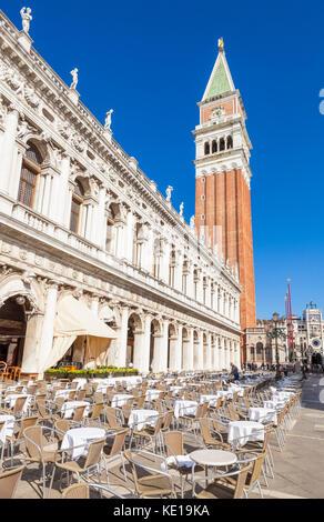 Venise ITALIE VENISE chaises vides et tables à un café restaurant place St Marc Piazza San Marco avec le campanile Banque D'Images