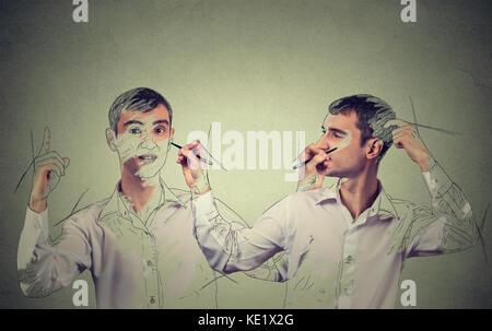 Créez vous-même concept. Bonne recherche jeune homme un dessin, une esquisse de lui-même sur fond de mur gris. visage Banque D'Images